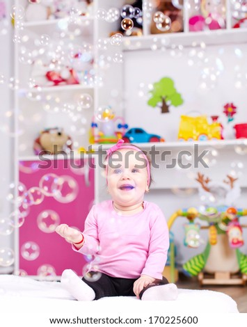 Baby girl playing with soap bubbles