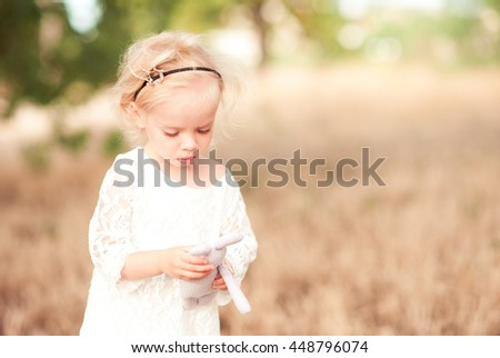 Baby girl playing with toy rabbit outdoors over nature background