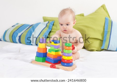 Baby girl playing with toys - stock photo