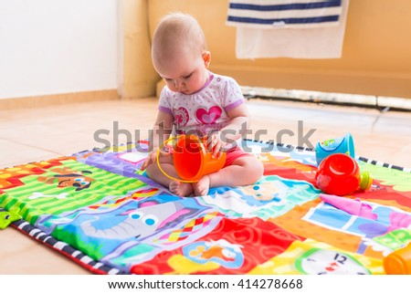 Baby girl playing with toys on the balcony - stock photo