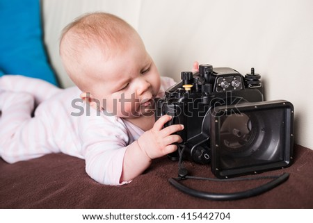 Baby girl playing with underwater camera - stock photo