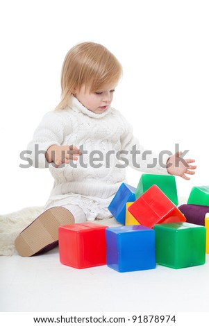 Baby girl plays with toy blocks over white background - stock photo