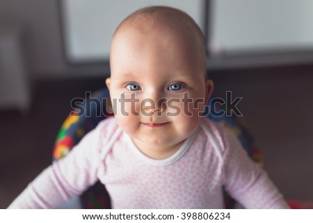 Baby girl portrait on the baby walker at home - stock photo