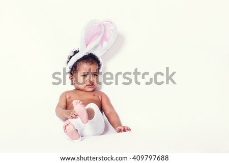 Baby girl portrait sitting and wearing bunny ears - stock photo