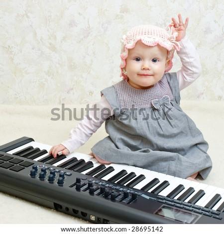 Baby girl posing with Electronic piano - stock photo