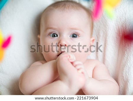 baby girl pulling foot to mouth - stock photo