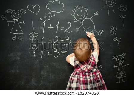 baby girl pupil draws a chalk on a blackboard - stock photo
