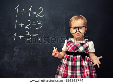 baby girl pupil in glasses and chalk at a school board with arithmetic examples - stock photo