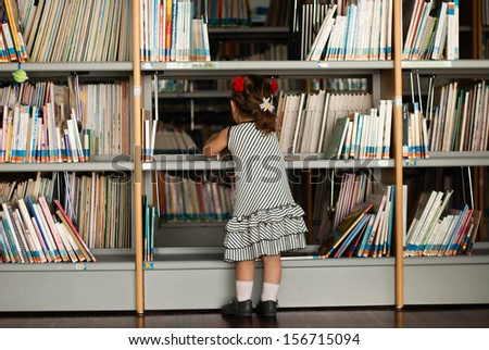 Baby girl reading book in library