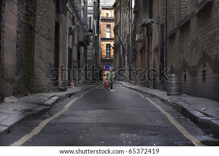 Baby girl running down a dark back alley - stock photo