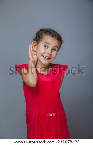 baby girl's hand to his ear listening on a gray background - stock photo