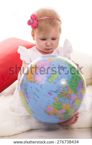 Baby girl search on world globe and sitting on fluffy blanket - stock photo