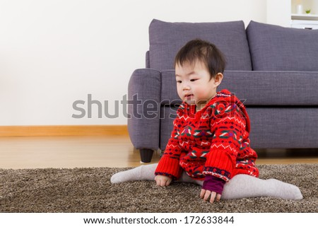 Baby girl seating on carpet