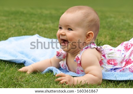 Baby, girl, seven-month-old child lying on a blue blanket