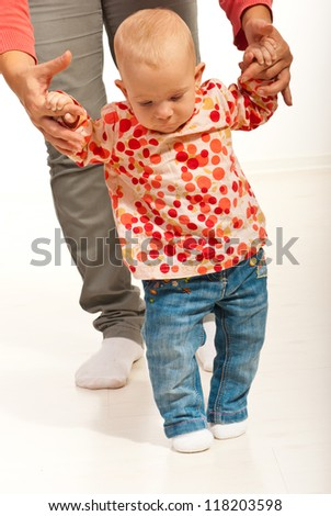 Baby girl seven months making first steps  with her mother on floor home - stock photo
