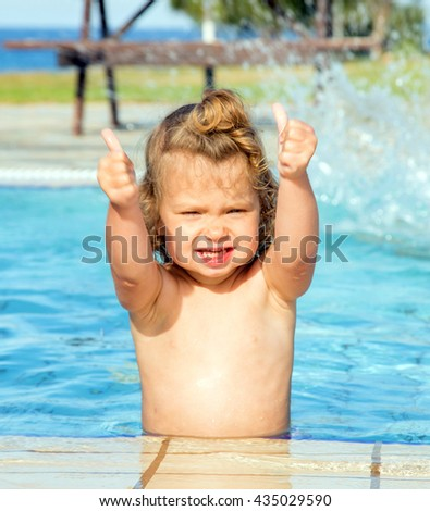 Baby girl showing thumbs up in the pool. Happy vacation concept.