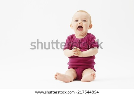 Baby girl sitting against white background