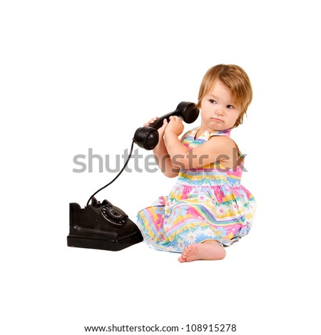 Baby girl sitting and calling in the antique phone. Retro style. Isolated on white background with clipping path