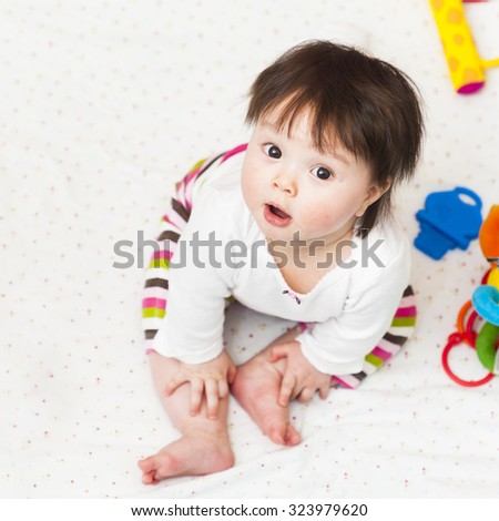 Baby girl sitting in playpen and looking up - stock photo