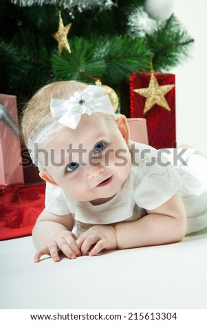 Baby girl sitting in red bag  with beckgraund from Christmas gift - stock photo