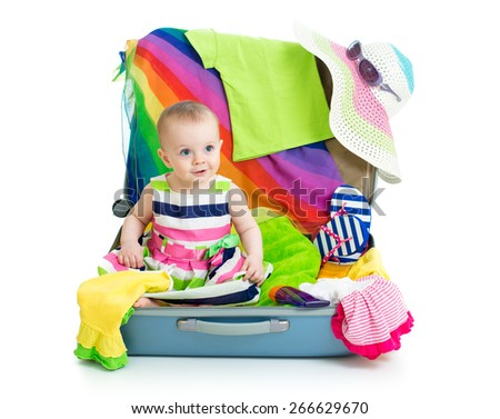 Baby girl sitting in suitcase with  things for vacation travel isolated