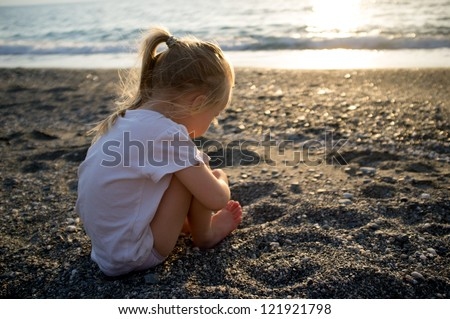 Baby girl sitting on a beach - stock photo