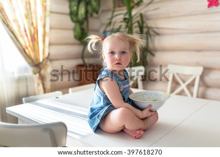 baby girl sitting on a table with a plate of porridge, independence, safety of children, naughty child, casual lifestyle photo series in real life interior, - stock photo
