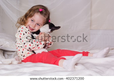 Baby girl sitting on bed and holding dog - stock photo