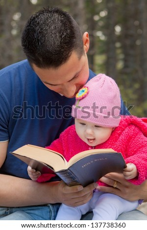 Baby girl sitting on dad�¢??s lap reading KJV Bible (King James Version) - stock photo