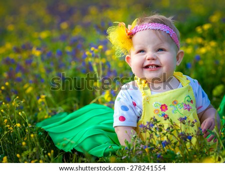 Baby girl sitting on green grass - stock photo