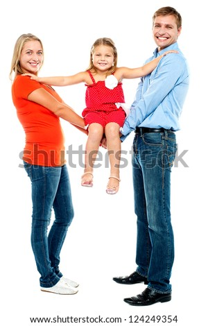 Baby girl sitting on outstretched arms of her parents. Enjoying the swing ride - stock photo