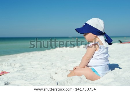Baby girl sitting on the beach looking at the ocean