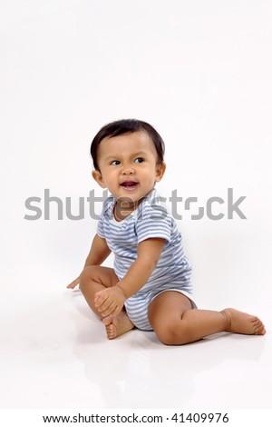 Baby girl sitting on white background, she looks cute - stock photo