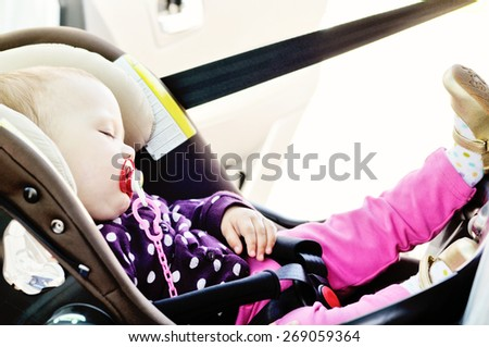 baby girl sleeping in the car seat - stock photo