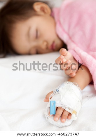 Baby girl sleeps on a bed in hospital with saline intravenous, selected focus.