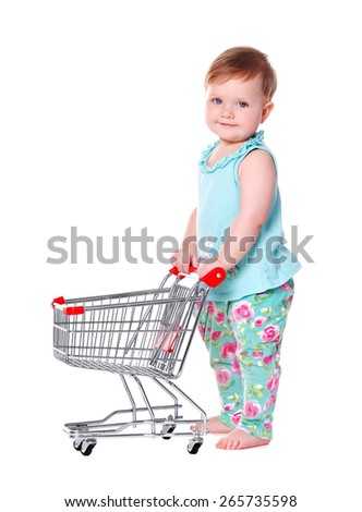 baby girl standing and holding shopping trolley - stock photo