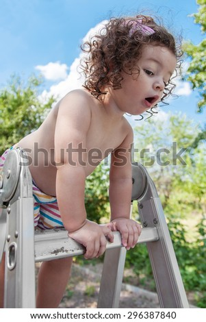 Baby girl standing on top stepladder outdoors - stock photo