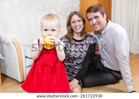 Baby girl standing with her parents sitting on the floor - stock photo