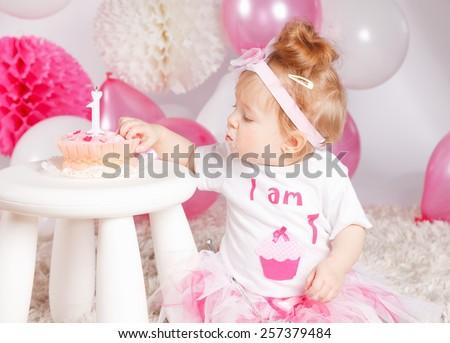 Baby girl tasting her birthday cake - stock photo