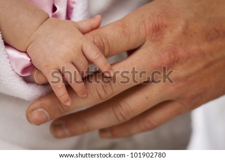 Baby Girl Tiny Hand Holding Rough Finger of Dad. - stock photo