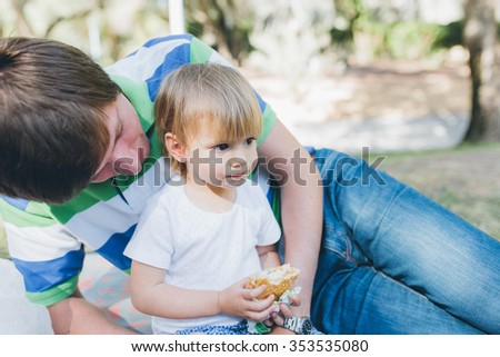 Baby girl toddler eating a sandwich outdoors in the park lying near her father