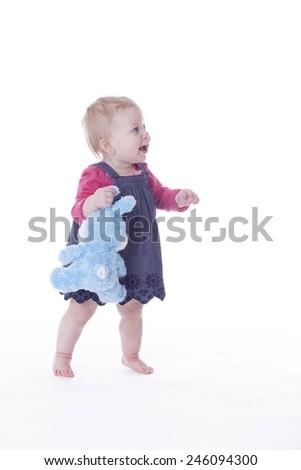 baby girl walking on white background - stock photo