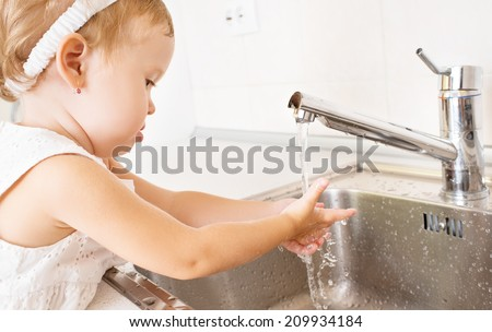 baby girl washes her hands in the bathroom with running water - stock photo