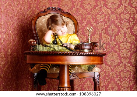 Baby girl, wearing in a suit of bees sitting on an old chair calling in the antique phone. Retro style