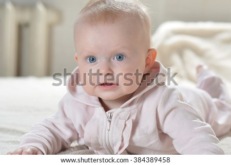 Baby girl wearing pink bathrobe and lying in her bed looking away - stock photo