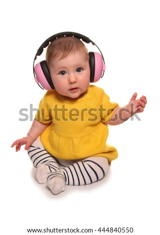 Baby girl wearing pink ear defenders cutout