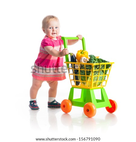baby girl with a basket of products from the supermarket on a white background isolated - stock photo