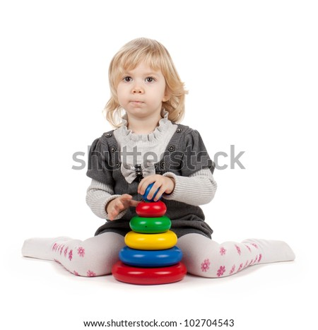 Baby girl with a toy pyramid. Isolated on white background