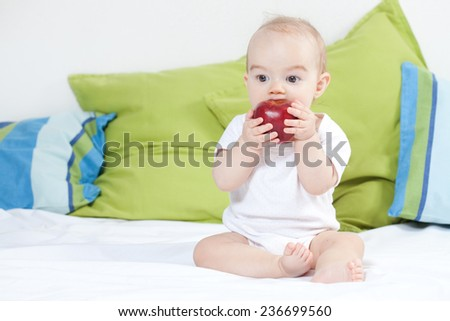 Baby girl with apple - stock photo