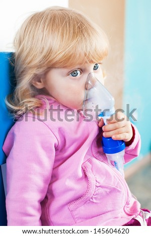 Baby girl with asthma problems making inhalation with mask on her face  - stock photo